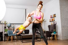Mother exercising with her baby son at home. Mother in sportswear swinging her baby son during the exercise at home royalty free stock photos
