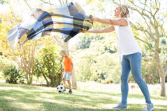 Mother spreading the picnic blanket while son playing football in background. On a sunny day Stock Photography