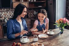 Mother spreading toast with with chocolate paste. Portrait of caring mother spreading toast with chocolate paste for her daughter in the kitchen Stock Images