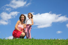 Mother squatting alongside with daughter. Holds it for hand and laughs stock images