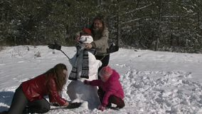 Mother of squatting alongside daughter and snowman. Mom and two daughters in the winter forest of snow a snowman. Mom put on the snowman's scarf. Family fun and stock footage