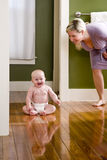 Mother standing beside happy baby sitting on floor stock photos
