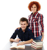 Mother standing near son's desk with hand on his shoulder. Studio shot of a mother standing near son's desk with hand on his shoulder, isolated over white Stock Image