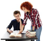 Mother standing near son's desk helping him doing his homework Stock Photography