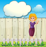 A mother standing near the wooden fence with an empty callout Royalty Free Stock Photos