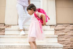 Mother standing on the stairs against the home outdoor saying goodbye to her daughter as she leave for kindergarten. Cute happy. Little girl wears backpack royalty free stock images