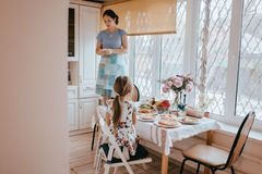 Mother is standing on the stool and making photo of the kitchen table with different courses for the breakfast and her stock photography