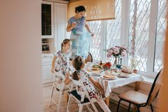 Mother is standing on the stool and making photo of the kitchen table with different courses for the breakfast and her royalty free stock photo