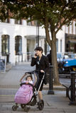 A mother standing with a stroller in the street, talking on her mobile phone Royalty Free Stock Photography