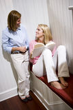 Mother standing beside teenage daughter reading Stock Photos