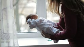 Mother stands near the window and cradles newborn.