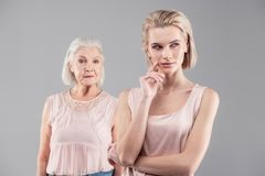 Thoughtful young woman with bob haircut looking aside. Mother staying behind. Thoughtful young women with bob haircut looking aside while her mother suspect royalty free stock photo