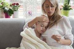 Mother staying at home with her sick child. Worried mother staying at home with her sick child stock photography