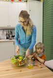 Mother stirring vegetable salad. Her little son standing near Royalty Free Stock Image