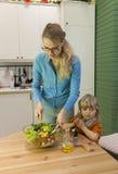 Mother stirring vegetable salad. Royalty Free Stock Image