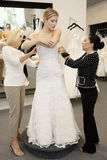 Mother and store employee assisting young woman getting dressed in bridal store Stock Images