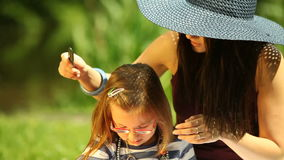 Mother in straw hat combing daughter in the park Stock Photo