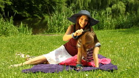 Mother in straw hat combing daughter in the park Royalty Free Stock Photos