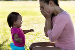 Mother stressed out while baby is crying. 2 year old girl crying to her stressed mother Royalty Free Stock Photos