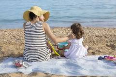 Mother stroking daughter on beach stock photo