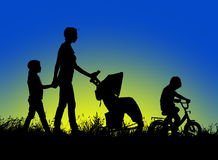 Mother with stroller and children walking at sunset Royalty Free Stock Image