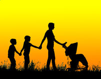 Mother with stroller and childrens walking at sunset Royalty Free Stock Photography