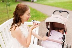 Mother with stroller and smartphone at summer park Royalty Free Stock Photos