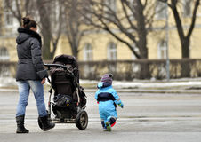 Mother with stroller walking near little son Royalty Free Stock Images