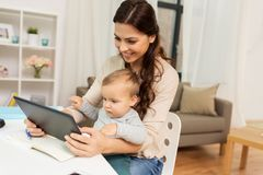 Mother student with baby and tablet pc at home. Multi-tasking, education, motherhood and technology concept - happy mother student with baby and tablet pc Stock Image