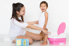 Mother successfully teaches child potty training. Mother pointing at potty, child happy at succeeding Stock Images