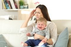 Mother suffering and baby crying desperately royalty free stock photo