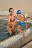 Mother and sun at the swimming pool Stock Image