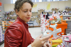 Mother in supermarket chooses children's footwear Royalty Free Stock Image