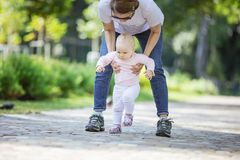 Mother supporting baby daughter and helping her make first steps stock photos
