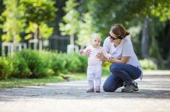 Mother supporting baby daughter and helping her make first steps royalty free stock image