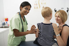 Mother Supporting Boy Receiving Injection. Portrait of a happy nurse injecting vaccine on boy's arm while mother supporting him royalty free stock images