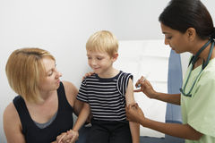 Mother Supporting Son Receiving Injection. Mother supporting young happy son receiving injection in clinic stock photo