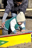 Mother supports child on sandbox. With help hands Stock Photo
