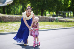 Mother supports the little daughter who learns to ride the scoot Royalty Free Stock Image