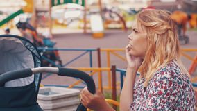 Mother sway baby carriage on children playground and speaking on phone. Summer. Mother sway baby carriage on children playground and speaking on phone. Summer stock video footage