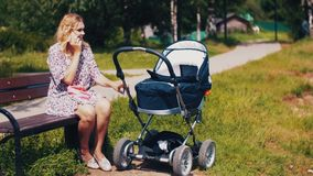 Mother sway baby carriage and speaking on phone on bench in summer park. Sunny. stock footage