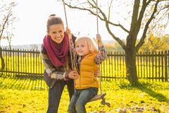 Mother swinging child outdoors Stock Photo