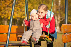Mother swinging with daughter in park Stock Photography