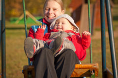 Mother swinging with dughter in autumn park Stock Photo