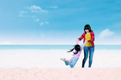 Mother swinging her child on the beach Royalty Free Stock Image