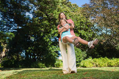 Mother swinging her daughter around having fun Stock Photo