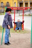 Mother swinging her son Royalty Free Stock Image