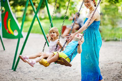 Mother swinging kids. Happy mother swinging her kids in the park Royalty Free Stock Photography