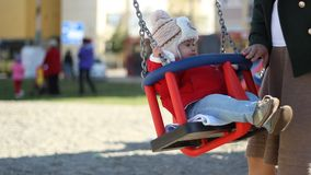 Mother Swings Children. Mother push the little baby with hat in swing, in the playground stock footage