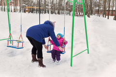 Mother swings her daughter on a swing on a winter afternoon outdoors in the Park Royalty Free Stock Photography